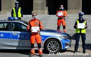 policjanci i ratownicy medyczni stoją obok siebie w ręce trzymając kartkę z napisem #murem za medykiem